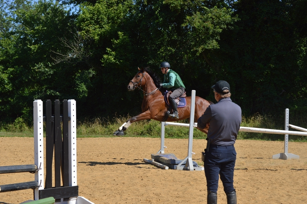 YEH trainer candidate Richard Lamb takes a green horse over a liverpool jump while instructor Robin Walker supervises