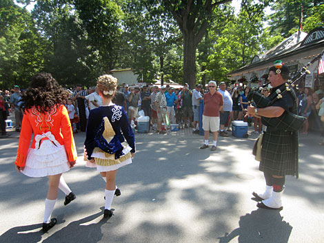 Irish step dancers perform to a bagpiper as horse racing fans line up to enter Saratoga.